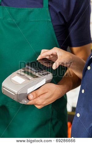 Female customer paying with mobilephone using NFC technology in hardware store