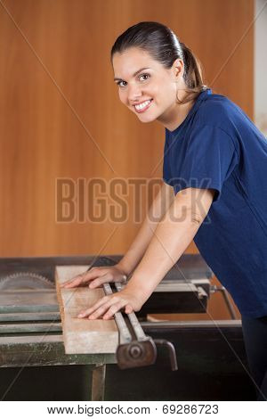 Side view portrait of young female carpenter using tablesaw in workshop