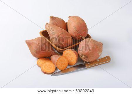 batata sweet potatoes and kitchen knife on white background