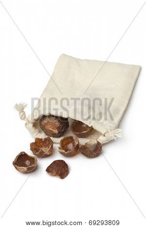 Nutshells of soapnuts in a cotton bag on white background