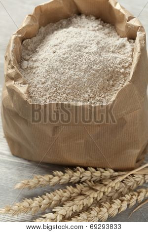 Dried wheat and wheat flour in a paper bag