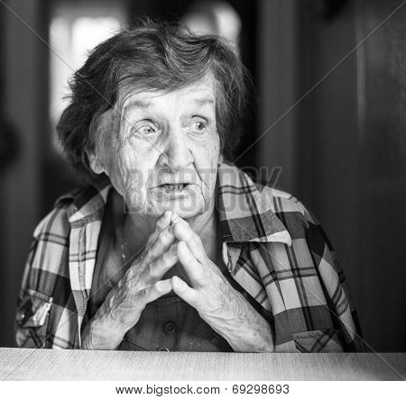 Emotional old woman sitting at table in his house (black and white photo)
