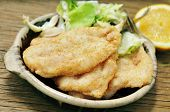 stock photo of hake  - an earthenware plate with some fried hakes and salad on a rustic wooden table - JPG