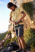 stock photo of harness  - Man with dreadlocks putting on his harness to go rock climbing - JPG