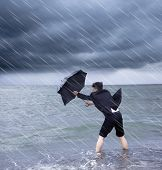 foto of stop fighting  - business man holding a umbrella to resist rainstorm - JPG