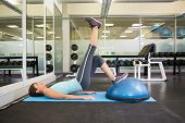 foto of pelvis  - Fit brunette using bosu ball to work out at the gym - JPG