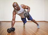 picture of bald man  - Full length of a muscular man doing push ups with dumbbells in gym - JPG