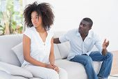stock photo of argument  - Attractive couple having an argument on couch at home in the living room - JPG