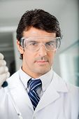 stock photo of protective eyewear  - Portrait of confident male scientist in protective eyewear at laboratory - JPG