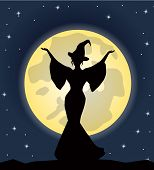 stock photo of moonlit  - beautiful witch standing against the background of the moonlit night - JPG