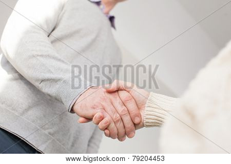 Handshake of adult man and youg woman