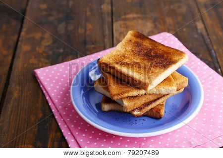 Toast bread on blue plate with pink napkin, on wooden table background