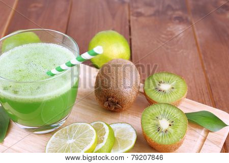 Glass of fresh lime juice with pieces of lime and kiwi on cut board and wooden table background