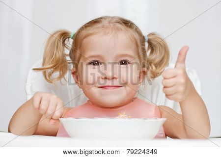 Happy Little Girl Eats With A Spoon While Sitting At Table