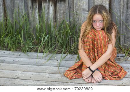 Young hippie girl sitting on the ground outdoors. Picture with space for text.
