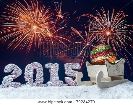 Frosted 2015 New Year digits and big glistering ball in wooden sleigh over dark blue sky with fireworks