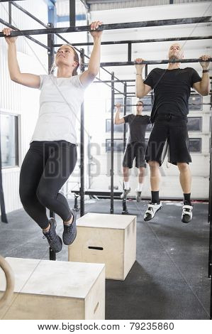 Workout team trains pullups at fitness gym
