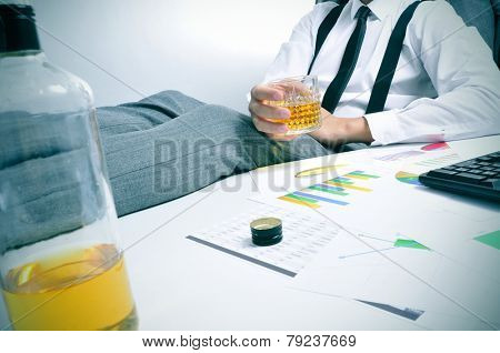 a young businessman sitting at his office desk with a glass with an alcoholic beverage in his hand