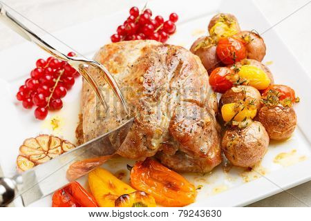Tasty roasted loin pork with potatoes, bell peppers and gooseberries being sliced