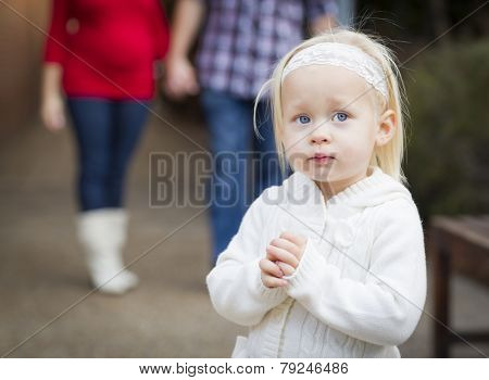 Adorable Little Girl with Her Mommy and Daddy Portrait Outside.