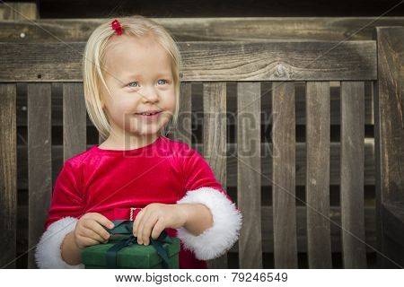 Adorable Little Girl Unwrapping Her Gift on a Bench Outside.