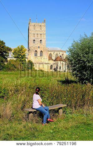Woman looking at Tewkesbury Abbey.