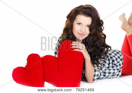 Beautiful brunette lying on the floor with a red heart in his hands.