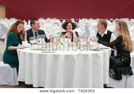 Five Young People At Round White Table In Restaurant. Dinner Party