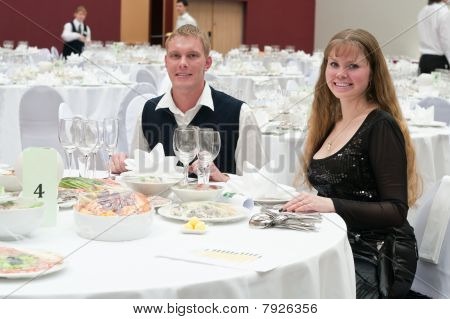 Loving Young Couple In Restaurant At Round White Table. Dinner Party