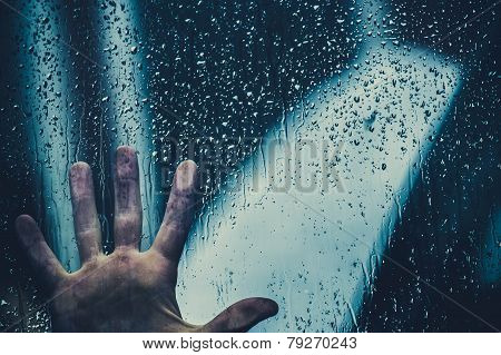 Hand on the glass after rain