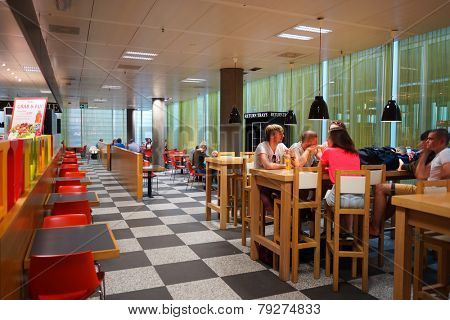 GENEVA - SEP 11: people in airport cafe on September 11, 2014 in Geneva, Switzerland. Geneva International Airport is located 4 km northwest of the city centre