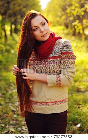 Young Redheaded Woman With Long Straight Hair In The Apple Garden