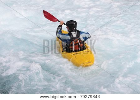 A man in kayak in Norwegian river. View from the back.
