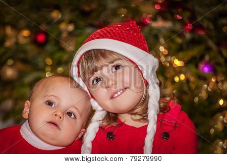 Brother and sister under Christmas tree