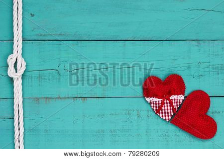 Red hearts and white rope border on antique teal blue woode background