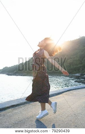 beautiful young woman jumping at sea side against sun lighting over sky