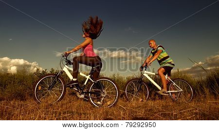 Sport couple riding bikes in field