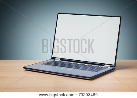 Laptop on desk with blank screen for copy or web page