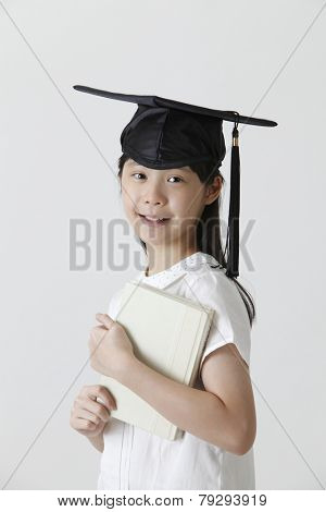 girl with the mortar board holding book