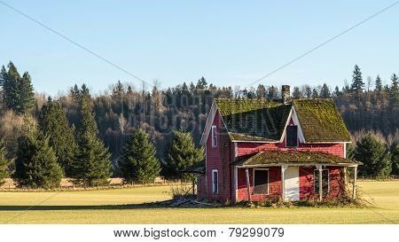 Dilapidated red house with moss covered roof