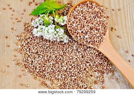 Buckwheat on board with flower and spoon