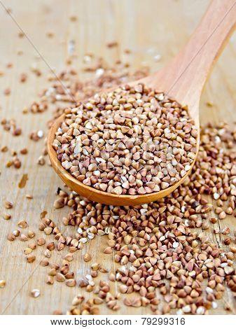 Buckwheat with spoon on wooden board