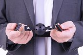 picture of sadomasochism  - Businessman holding ball gag - JPG