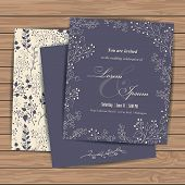 picture of announcement  - Wedding invitation cards with floral elements on wood plank background - JPG