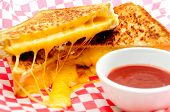 picture of ooze  - decadent grilled cheese sandwiches with oozing cheese running out with ketchup for dipping