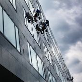 stock photo of window washing  - Climbers washing windows of a modern high - JPG