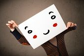 foto of smiley face  - Young woman holding a cardboard with a smiley face on it in front of her head - JPG
