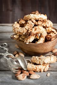 picture of crescent-shaped  - Homemade almond crescent cookies on old wood background - JPG