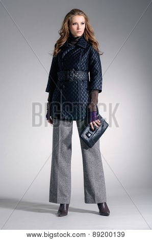full-length,fashion model clothes holding handbag posing-gray background
