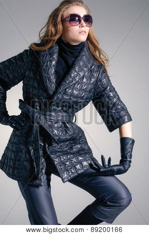Portrait of fashion model in fashion coat dress posing in the studio